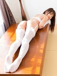 Shino Aoi striking seductive poses while in white lingerie and stockings in a room